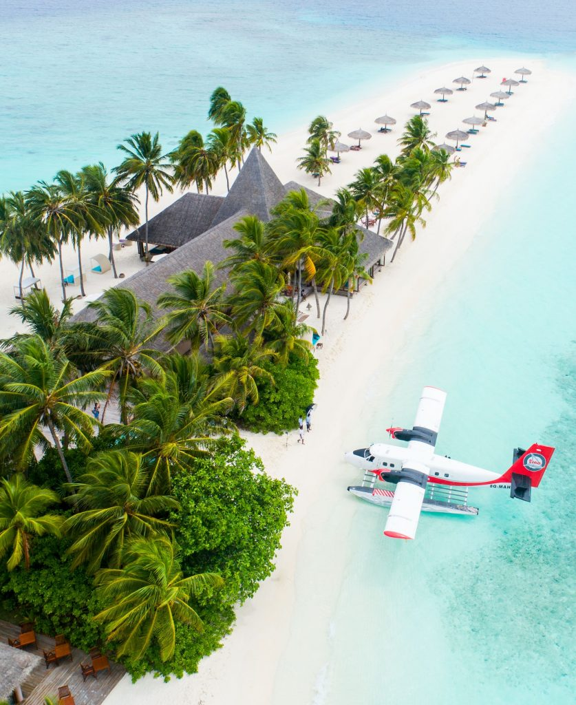 Maldives island with sea plane parked on shore